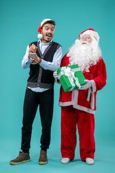 Vorderansicht weihnachtsmann mit jungem mann, der notizen auf dem blauen hintergrund macht