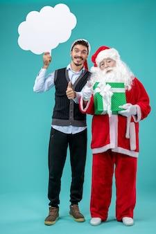 Vorderansicht-weihnachtsmann mit jungem mann, der weißes wolkenzeichen auf dem blauen hintergrund hält