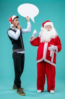 Vorderansicht-weihnachtsmann mit jungem mann, der weißes zeichen auf dem blauen hintergrund hält