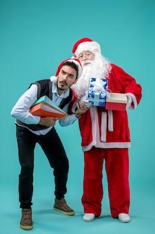 Vorderansicht weihnachtsmann mit jungem mann und präsentiert auf blauem boden kaltes weihnachtsferienschnee-neujahr