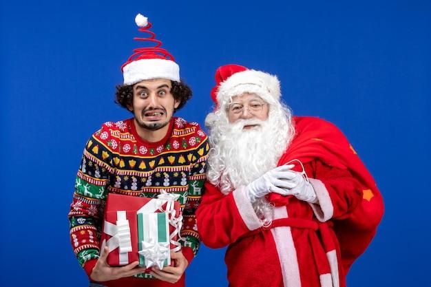 Vorderansicht weihnachtsmann mit jungem mann und verschiedenen geschenken auf blauer emotion weihnachtsfeiertagsfarbe