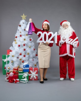 Vorderansicht weihnachtsmann mit jungen frau, die schriften auf dem grauen hintergrund hält und verkauft