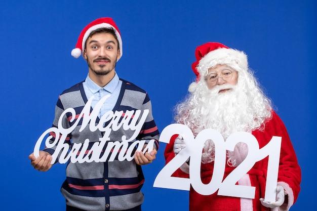 Vorderansicht weihnachtsmann mit jungen männlichen halten und frohen weihnachten schriften auf blauem weihnachtsfeiertag
