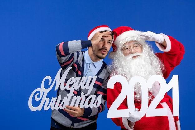 Vorderansicht weihnachtsmann mit jungen männlichen halten und frohen weihnachtsschriften auf dem blauen neuen jahr