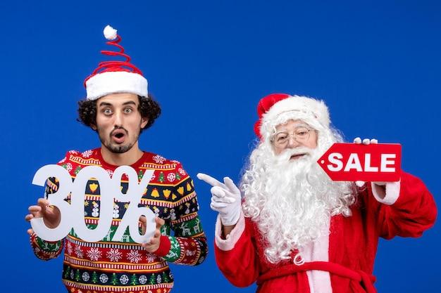 Vorderansicht weihnachtsmann mit jungen männlichen halten und verkaufsschriften auf blauer schneefarbe neujahr weihnachtsfeiertage