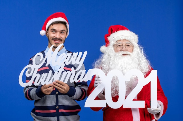 Vorderansicht weihnachtsmann mit jungen männlichen holding und frohe weihnachten schriften an blauen weihnachtsfeiertagen