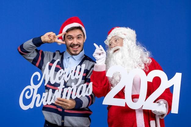 Vorderansicht weihnachtsmann mit jungen männlichen holding und frohe weihnachten schriften auf blau