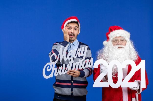 Vorderansicht weihnachtsmann mit jungen männlichen holding und frohe weihnachten schriften auf blauem weihnachten