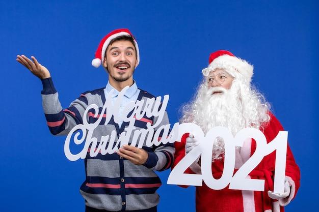 Vorderansicht weihnachtsmann mit jungen männlichen holding und frohe weihnachten schriften auf blauer weihnachtsfarbe