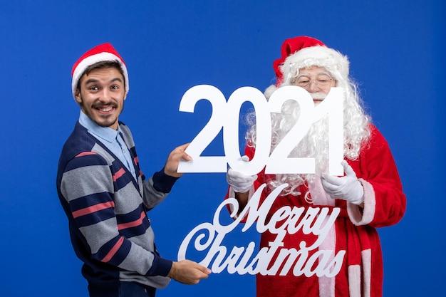 Vorderansicht weihnachtsmann mit jungen männlichen holding und frohe weihnachten schriften