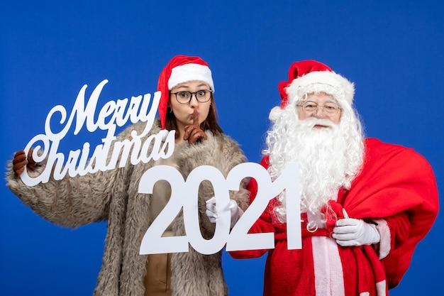 Vorderansicht weihnachtsmann mit junger frau, die frohe weihnachten und schriften über blaue farbe emotion urlaub weihnachten neues jahr hält