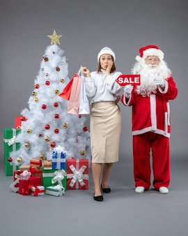 Vorderansicht weihnachtsmann mit junger frau um weihnachtsbaum und präsentiert auf dem grauen hintergrund