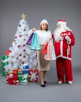 Vorderansicht weihnachtsmann mit junger frau um weihnachtsgeschenke auf grauem hintergrund