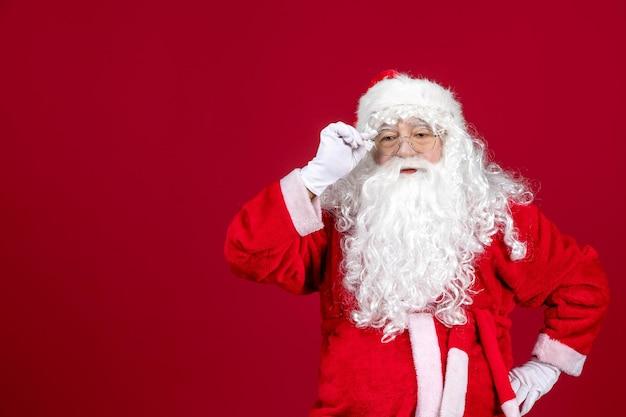 Vorderansicht weihnachtsmann mit klassischem weißen bären und roter kleidung auf rot