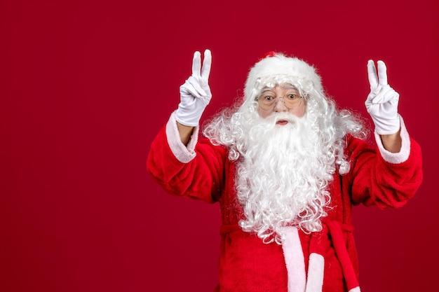 Vorderansicht weihnachtsmann mit klassischem weißen bären und roter kleidung auf rotem schreibtisch urlaub neues jahr
