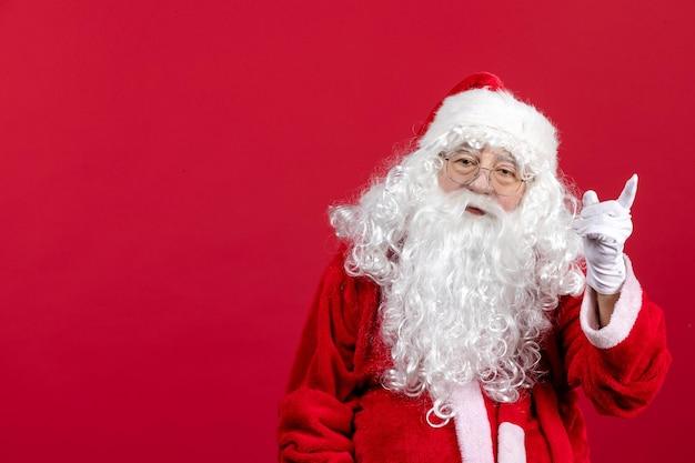 Vorderansicht weihnachtsmann mit klassischem weißen bären und roter kleidung, die auf rotem weihnachtsneujahr steht