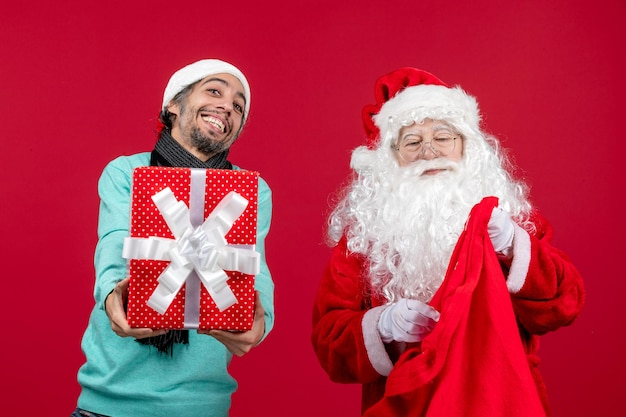 Vorderansicht weihnachtsmann mit männlichem geschenk aus tasche auf rotem schreibtisch geschenk xmas emotion red