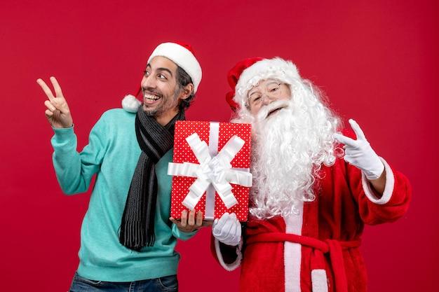 Vorderansicht-weihnachtsmann mit männlichem holding-feiertagsgeschenk auf dem roten geschenk-emotion-rot-weihnachten
