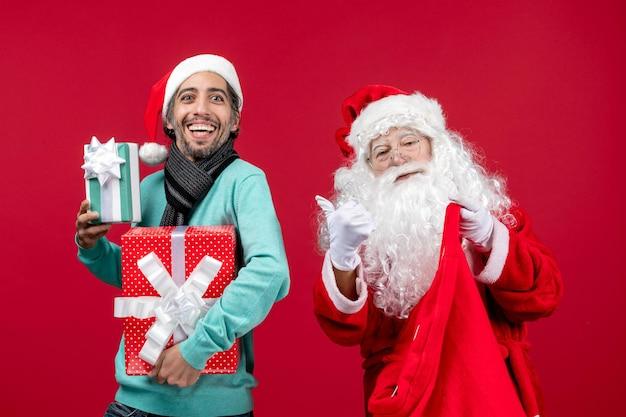 Vorderansicht weihnachtsmann mit männlichen geschenken aus tasche auf rotem rotem geschenk weihnachten emotion neues jahr