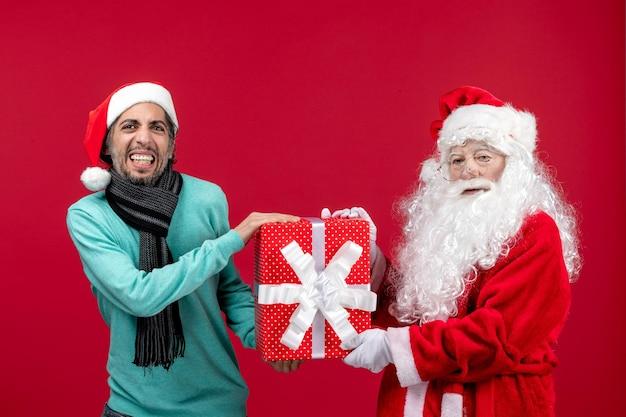 Vorderansicht weihnachtsmann mit männlichen halten feiertagsgeschenk auf dem roten roten geschenk weihnachten emotion neues jahr