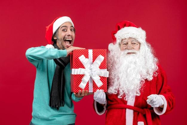 Vorderansicht weihnachtsmann mit männlichen halten feiertagsgeschenk auf rotem emotionen rotes geschenk weihnachten neues jahr