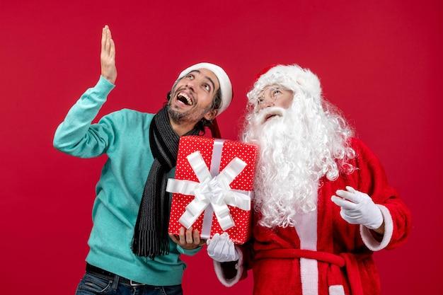 Vorderansicht weihnachtsmann mit männlichen halten feiertagsgeschenk auf rotem geschenk emotionen rotes weihnachten neues jahr