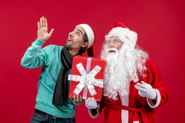 Vorderansicht weihnachtsmann mit männlichen halten feiertagsgeschenk auf roten geschenken emotion rotes weihnachten neues jahr