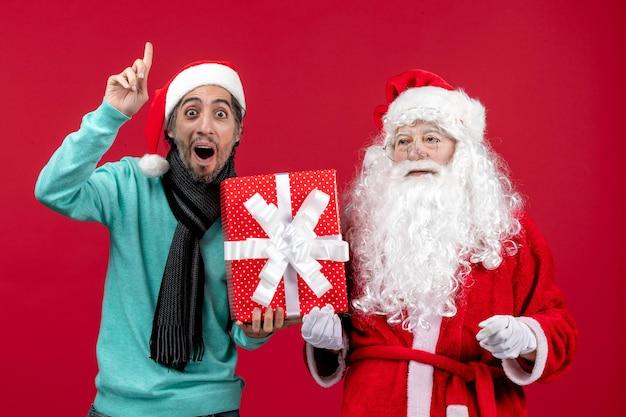 Vorderansicht weihnachtsmann mit männlichen holding feiertagsgeschenk auf rotem schreibtisch emotion rotes geschenk weihnachten