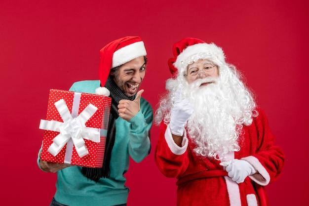 Vorderansicht weihnachtsmann mit männlichen holding urlaubsgeschenk auf rotem boden emotion rotes geschenk weihnachten