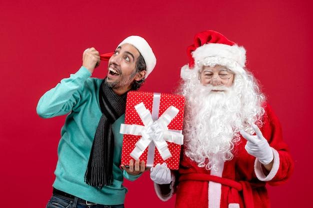 Vorderansicht weihnachtsmann mit männlichen holding urlaubsgeschenk auf rotem boden geschenk emotion rote weihnachten