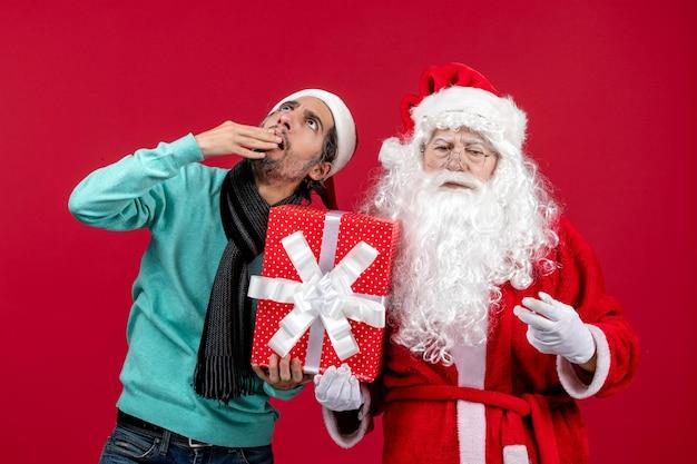Vorderansicht weihnachtsmann mit männlichen holding urlaubsgeschenk auf rotem geschenk emotion weihnachten neujahr rot