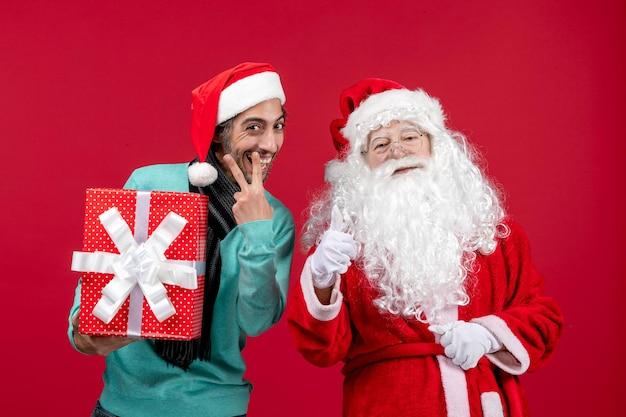 Vorderansicht weihnachtsmann mit männlichen holding urlaubsgeschenk auf rotem schreibtisch emotion rotes geschenk weihnachten neues jahr