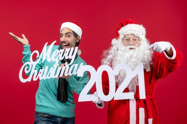 Vorderansicht weihnachtsmann mit männlicher holding und frohe weihnachten schriften auf rotem weihnachtsgefühl