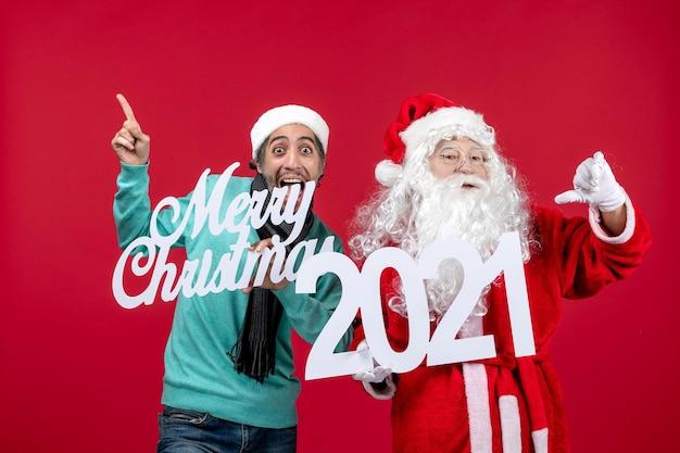 Vorderansicht weihnachtsmann mit männlicher holding und frohe weihnachten schriften auf rotem weihnachtsneujahr