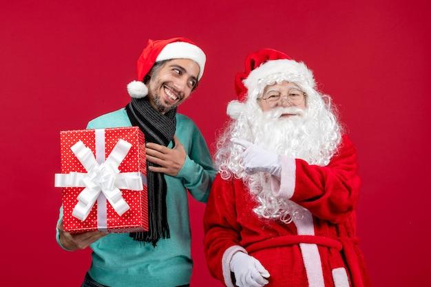 Vorderansicht weihnachtsmann mit mann, der feiertagsgeschenk auf rotem emotion rotem geschenk weihnachten neues jahr hält