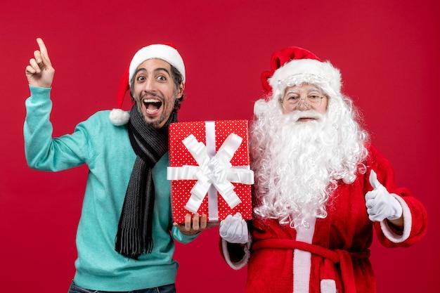 Vorderansicht weihnachtsmann mit mann, der feiertagsgeschenk auf rotem geschenkgefühl rotes weihnachten neues jahr hält