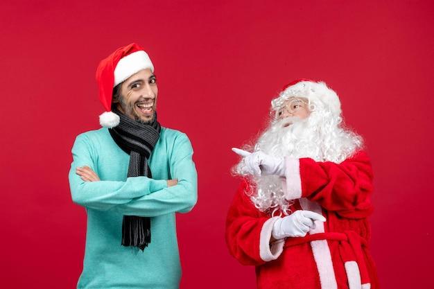 Vorderansicht weihnachtsmann mit mann, der gerade auf rotem weihnachtsfeiertag steht, präsente emotion stimmung
