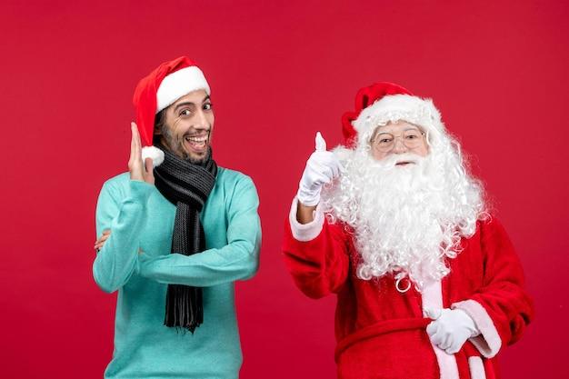 Vorderansicht weihnachtsmann mit mann, der gerade auf rotem weihnachtsfeiertag steht, präsente emotionen stimmung