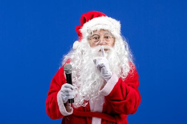 Vorderansicht weihnachtsmann mit rotem anzug und weißem bart, der mikrofon auf blauem neujahrsfest hält