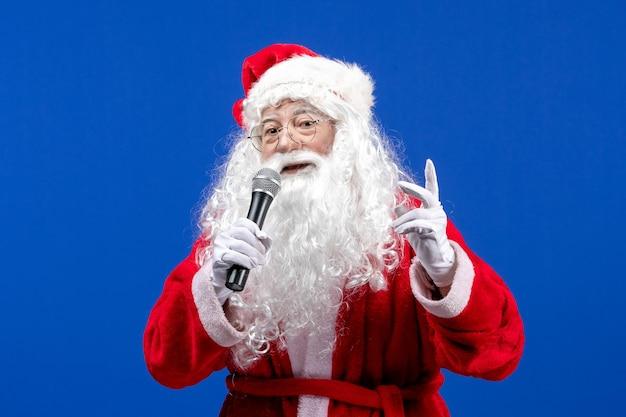 Vorderansicht weihnachtsmann mit rotem anzug und weißem bart, der mikrofon auf dem blauen weihnachtsemotionsurlaub des neuen jahres hält