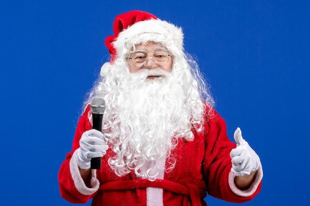 Vorderansicht weihnachtsmann mit rotem anzug und weißem bart mit mikrofon auf blauem neujahrsfeiertag