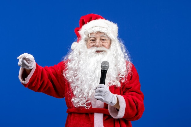 Vorderansicht weihnachtsmann mit rotem anzug und weißem bart mit mikrofon auf blauer weihnachtsfarbe des neuen jahres