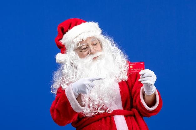 Vorderansicht weihnachtsmann mit roter bankkarte auf dem blauen weihnachtsgeschenk des neuen jahres
