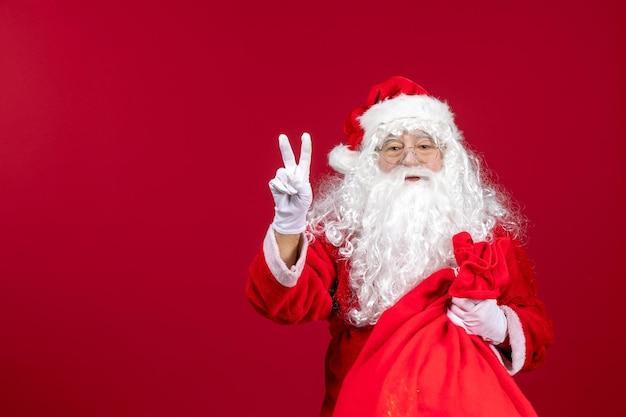 Vorderansicht weihnachtsmann mit roter tüte voller geschenke auf dem roten neujahrsfeiertagsweihnachtsgefühl