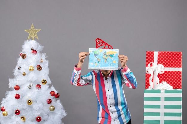 Vorderansicht-weihnachtsmann mit spiralfeder-weihnachtsmannmütze, die sein gesicht mit karte bedeckt