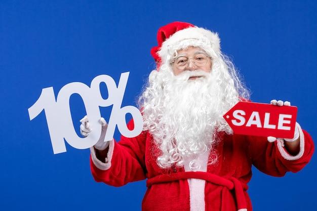 Vorderansicht weihnachtsmann mit verkauf und schriften auf blauem schnee urlaub neujahr weihnachten