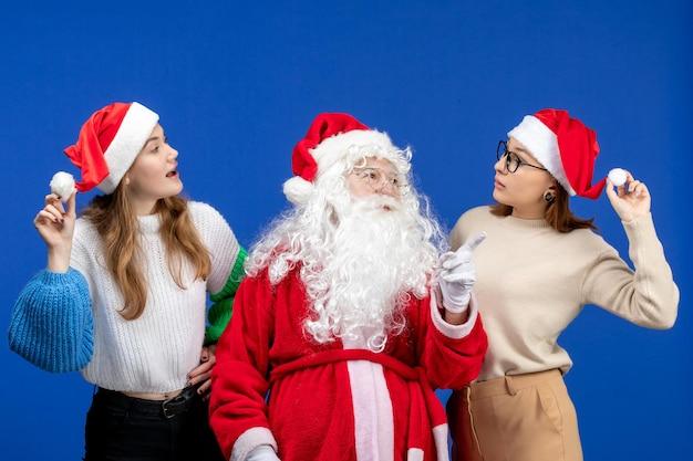 Vorderansicht weihnachtsmann mit weibchen an blauen feiertagen kalter weihnachtsschnee des neuen jahres