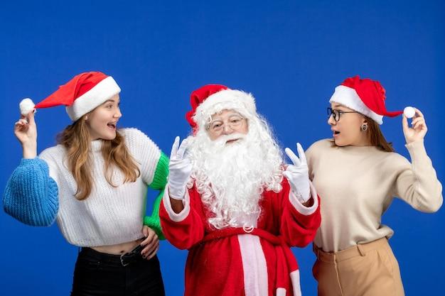 Vorderansicht weihnachtsmann mit weibchen an einem blauen feiertag kalten weihnachtsschnee des neuen jahres