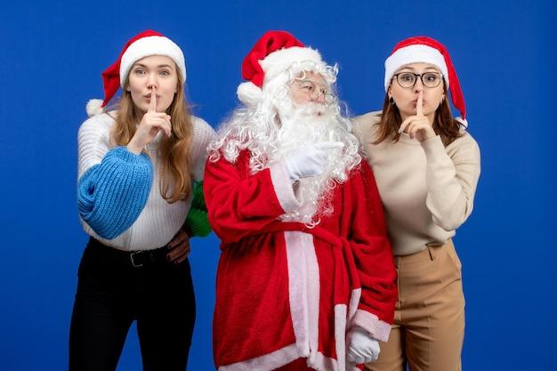 Vorderansicht weihnachtsmann mit weibchen auf blauem farbgefühl schnee neues jahr
