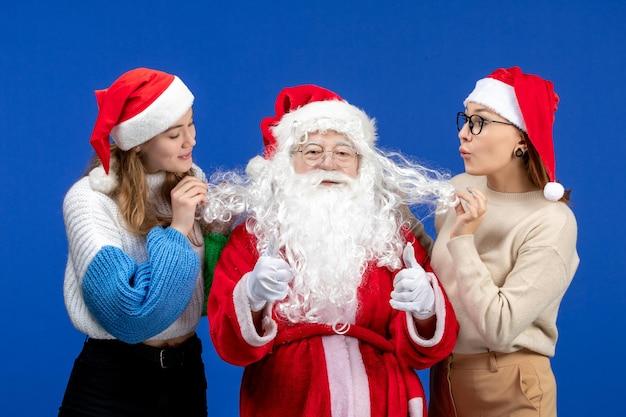 Vorderansicht weihnachtsmann mit weibchen auf blauem kaltem feiertagsweihnachtsgefühlsschnee